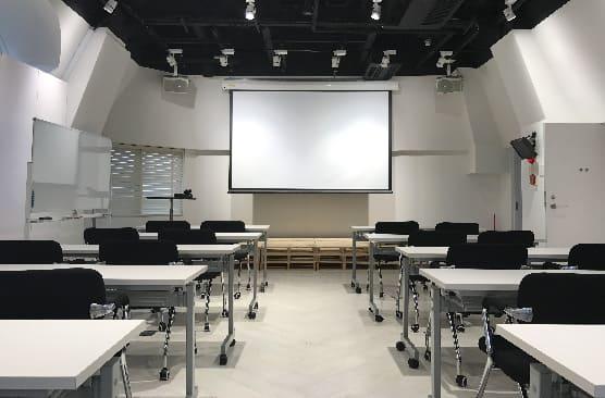 観客席に座った人が、空のスクリーンをモックアップして見ているプレゼンテーションホール。スピーカーと空のディスプレイは、モックアップを表します。トレーニングまたはフォーラムテンプレートに関する公開情報。