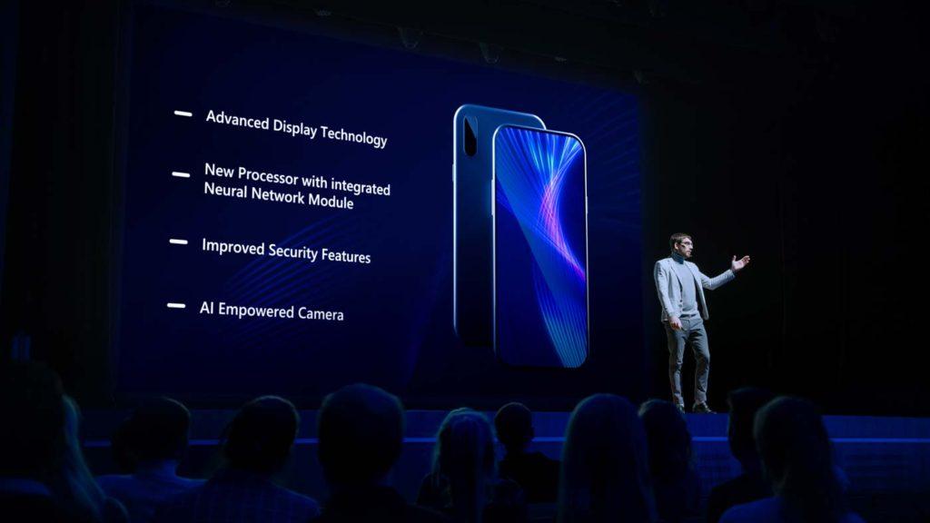 新製品を使ったライブイベントの公開: 基調講演者がスマートフォンの装置を観客に提示 映画館の画面に、ハイテク機能とトップハイライトを備えたモックアップタッチスクリーンフォンが表示される