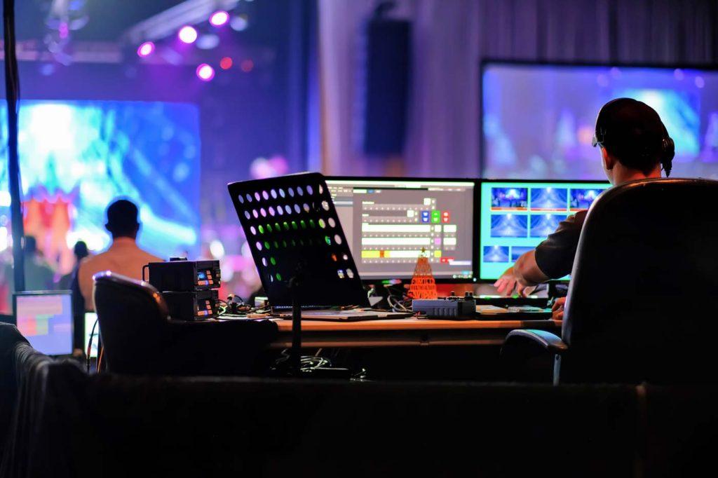 サウンドテクニシャンは、ナイトクラブのロックコンサートでオーディオミキサーのパネルに取り組んでいます。音楽会場の祭典でコントローラーを混ぜ合わせるプロフェッショナル。